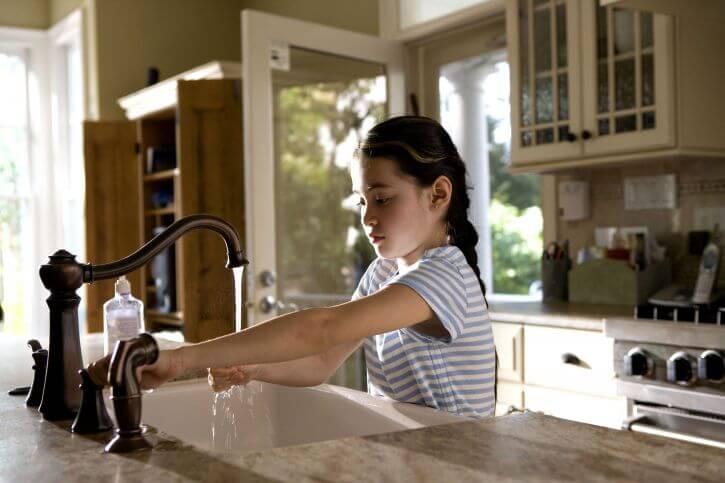 menina mexendo na torneira cobranca de agua individualizada em condominio