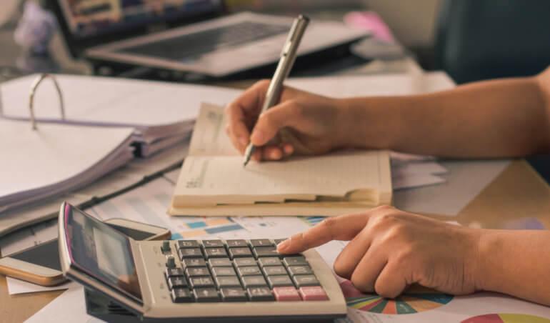 mao digitando na calculadora como verificar as contas do condominio
