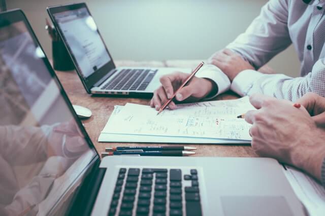 profissionais analisando um documento em frente aos computadores, trabalhando na manutenção predial de condomínios
