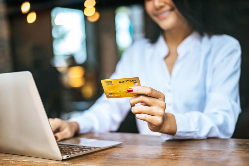 mulher com cartão de crédito na mão, fazendo a contabilidade de condomínio