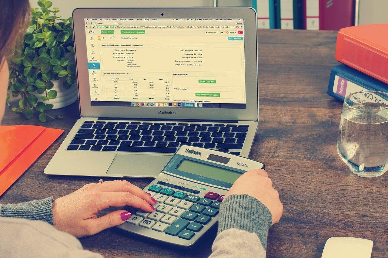 pessoa com calculadora e computador para realizar a contabilidade de condomínio