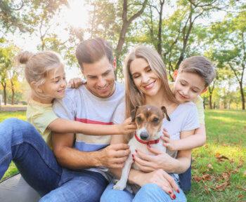 mãe, pai e filhos com um cachorrinho, que pode ser incluído no espaço pet em condomínios