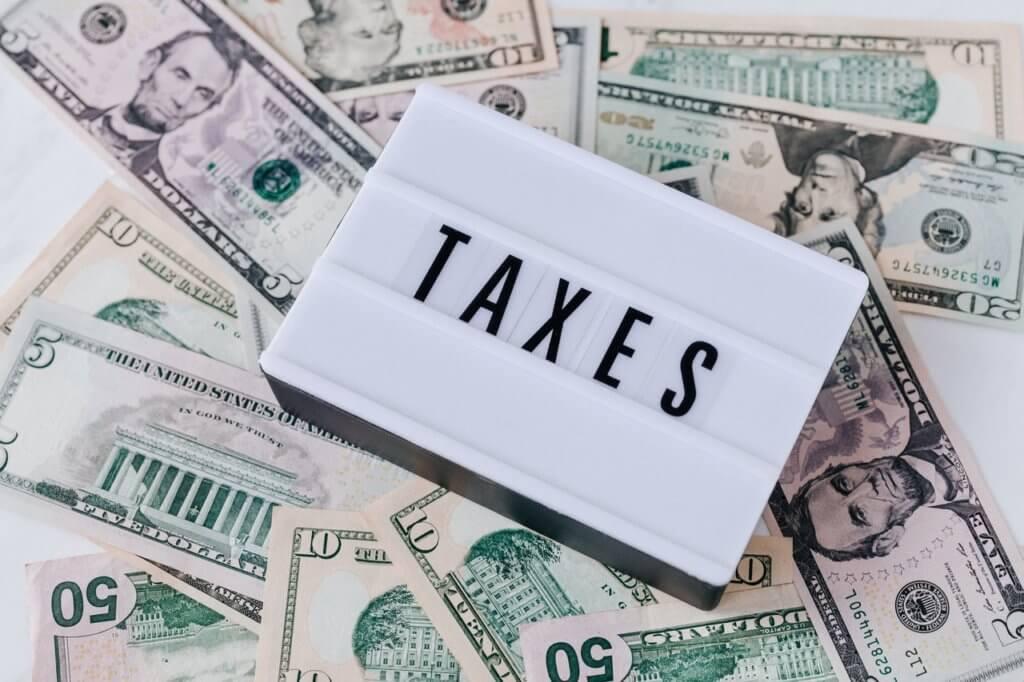 dinheiro em dólares e um quadro escrito taxes para simbolizar uma taxa de condomínio