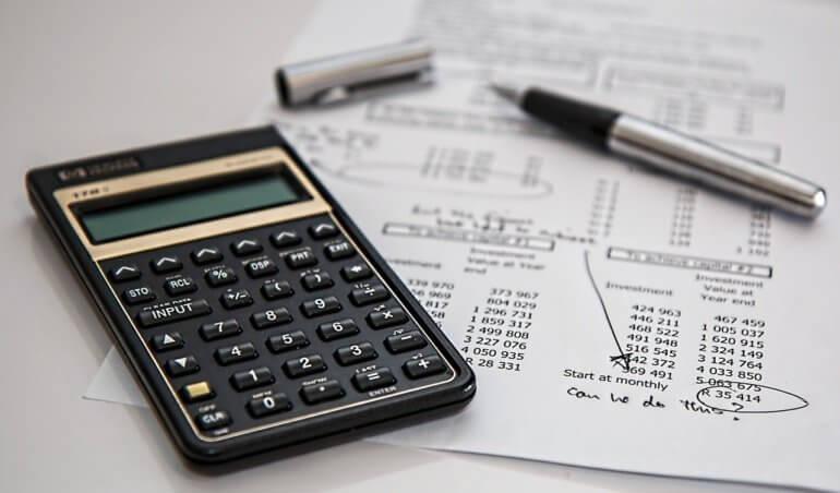 calculadora, caneta e relatório para calcular a taxa de condomínio